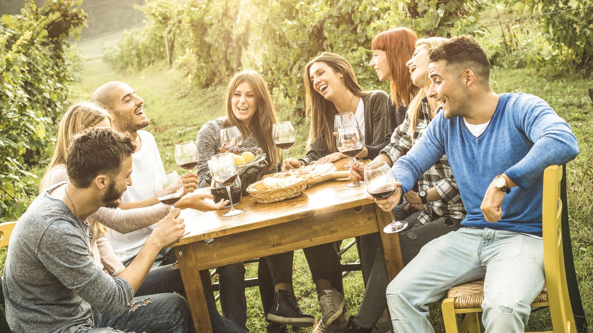 Leute sitzen im Weingarten und lachen